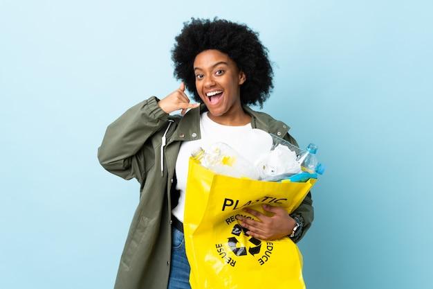 Młoda amerykanin afrykańskiego pochodzenia kobieta trzyma przetwarzającą torbę na kolorowej ścianie robi telefonu gestowi. oddzwoń do mnie znak