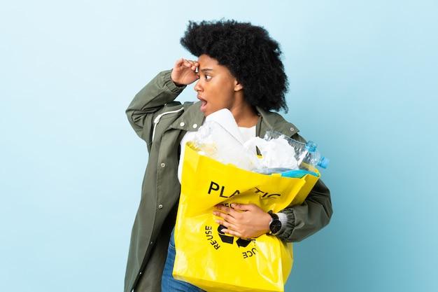 Młoda amerykanin afrykańskiego pochodzenia kobieta trzyma przetwarzającą torbę na kolorowej ścianie z niespodzianki wyrażeniem podczas gdy patrzejący stronę