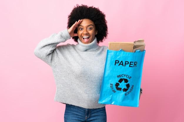 Młoda amerykanin afrykańskiego pochodzenia kobieta trzyma przetwarzającą torbę na kolorowej ścianie z niespodzianki wyrażeniem