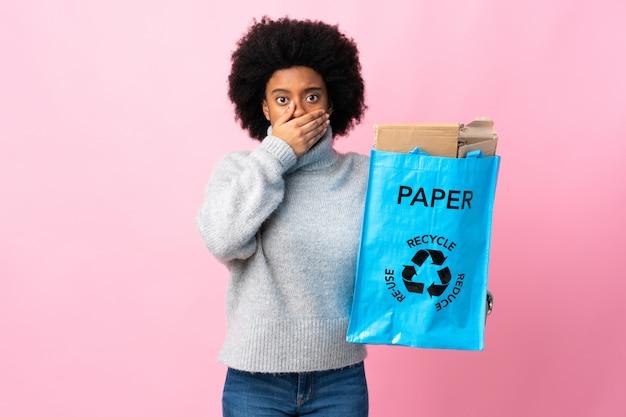 Młoda amerykanin afrykańskiego pochodzenia kobieta trzyma przetwarzającą torbę na kolorowym ściennym nakrywkowym usta z ręką