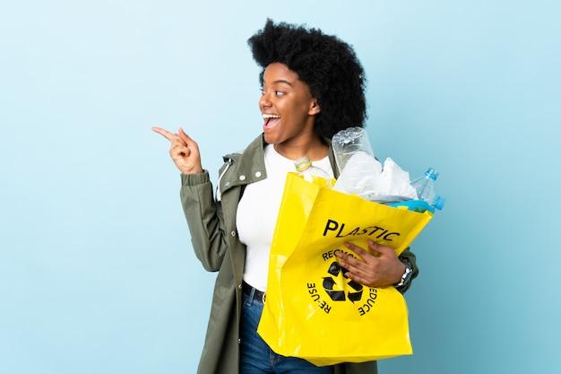 Młoda amerykanin afrykańskiego pochodzenia kobieta trzyma przetwarzającą torbę odizolowywająca na kolorowej ścianie zamierza realizować rozwiązanie podczas gdy podnoszący palec w górę