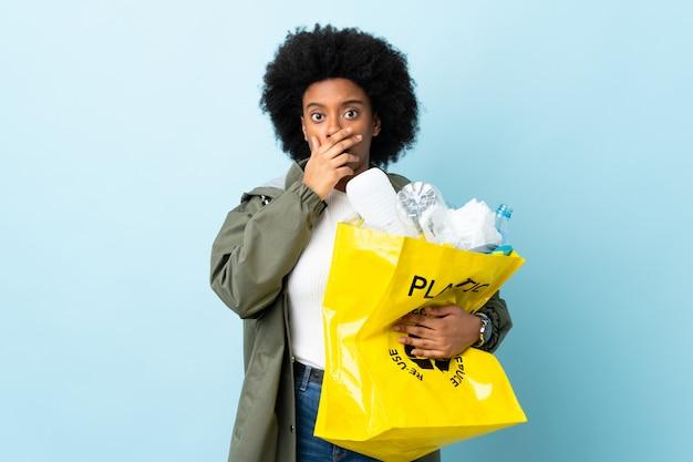 Młoda amerykanin afrykańskiego pochodzenia kobieta trzyma przetwarzającą torbę odizolowywająca na kolorowej ścianie zaskakującej i szokującej podczas gdy patrzejący dobrze