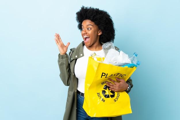 Młoda amerykanin afrykańskiego pochodzenia kobieta trzyma przetwarzającą torbę odizolowywająca na kolorowym tle z niespodzianka wyrazem twarzy