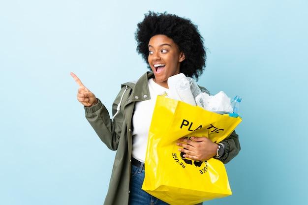 Młoda amerykanin afrykańskiego pochodzenia kobieta trzyma przetwarzającą torbę odizolowywająca na kolorowym tle zaskakującym i wskazuje stronę