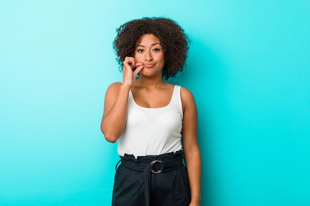Młoda amerykanin afrykańskiego pochodzenia kobieta trzyma sekret z palcami na wargach.