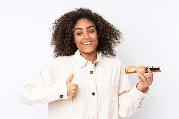 Młoda amerykanin afrykańskiego pochodzenia kobieta trzyma suszi na białej ścianie z aprobatami, ponieważ stało się coś dobrego