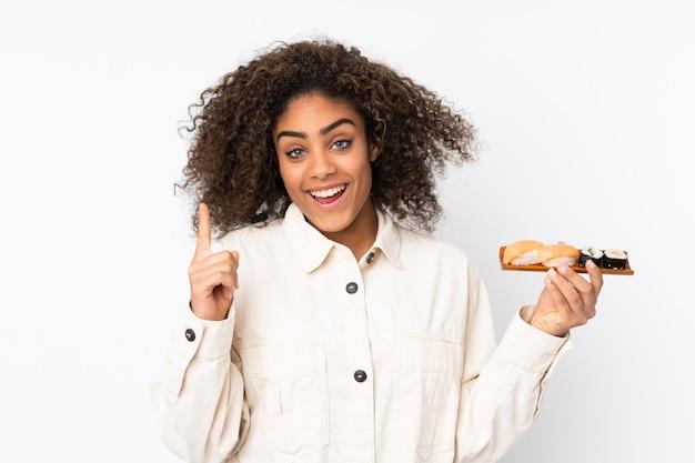 Młoda amerykanin afrykańskiego pochodzenia kobieta trzyma suszi na biel ścianie wskazuje w górę doskonałego pomysłu