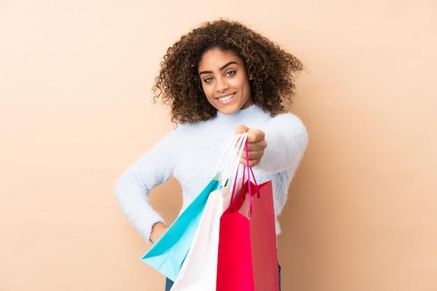 Młoda amerykanin afrykańskiego pochodzenia kobieta trzyma torby na zakupy i daje im na beżowej ścianie
