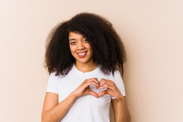 Młoda amerykanin afrykańskiego pochodzenia kobieta uśmiecha się kierowego kształt z rękami i pokazuje.