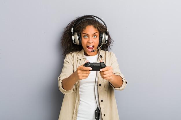 Młoda amerykanin afrykańskiego pochodzenia kobieta używa hełmofony i kontroler gier