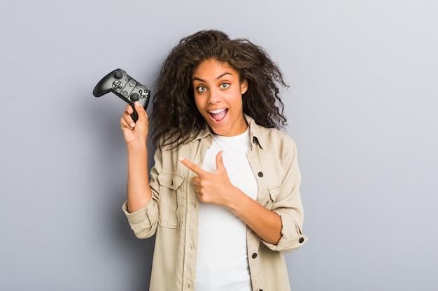 Młoda amerykanin afrykańskiego pochodzenia kobieta używa hełmofony i kontrolera gier