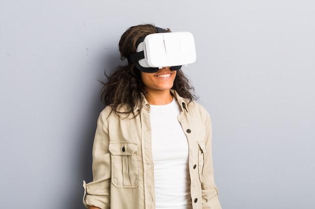 Młoda amerykanin afrykańskiego pochodzenia kobieta używa rzeczywistość wirtualna szkła