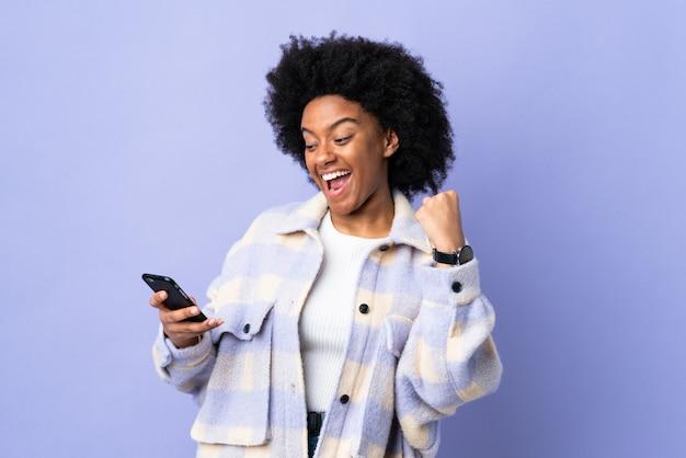 Młoda amerykanin afrykańskiego pochodzenia kobieta używa telefon komórkowego odizolowywającego na purpurach izoluje świętuje zwycięstwo
