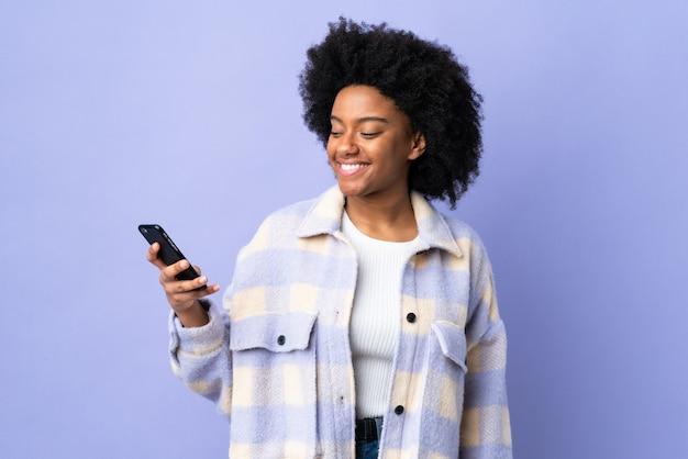 Młoda amerykanin afrykańskiego pochodzenia kobieta używa telefon komórkowego odizolowywającego na purpurach izoluje z szczęśliwym wyrażeniem