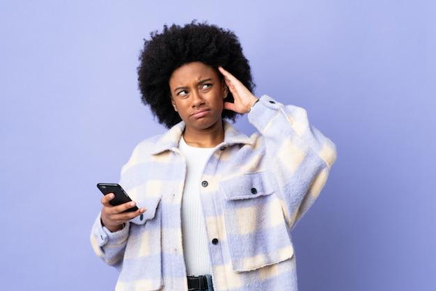 Młoda amerykanin afrykańskiego pochodzenia kobieta używa telefon komórkowego odizolowywającego na purpurowym tle ma wątpliwości z zmieszanym twarzy wyrażeniem