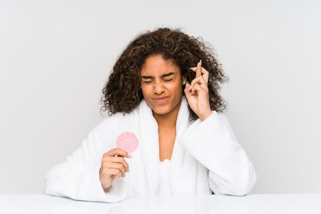 Młoda amerykanin afrykańskiego pochodzenia kobieta używa twarzowego dyska skrzyżowanie dotyka palce dla mieć szczęście