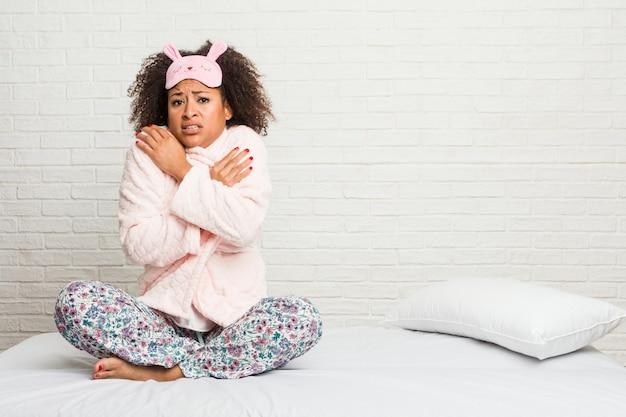 Młoda amerykanin afrykańskiego pochodzenia kobieta w łóżku jest ubranym pijama iść zimno z powodu niskiej temperatury