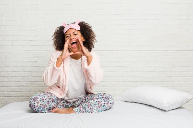 Młoda amerykanin afrykańskiego pochodzenia kobieta w łóżku jest ubranym pijama krzyczeć podekscytowanego do przodu.