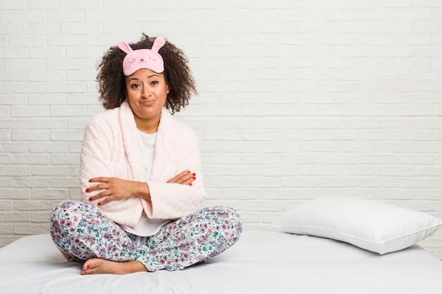 Młoda amerykanin afrykańskiego pochodzenia kobieta w łóżku jest ubranym pijama nieszczęśliwego patrzeć z sarkastycznym wyrażeniem.