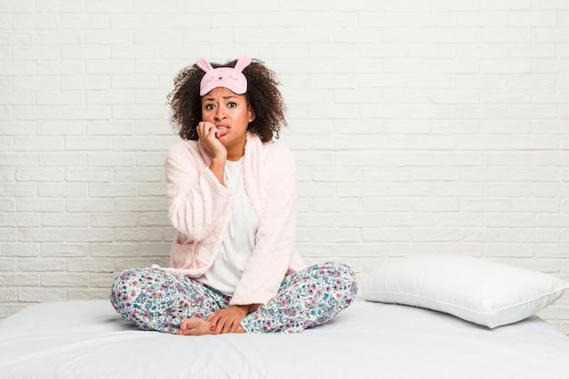 Młoda amerykanin afrykańskiego pochodzenia kobieta w łóżku jest ubranym pijama obgryzających paznokcie, nerwowa i bardzo niespokojna.