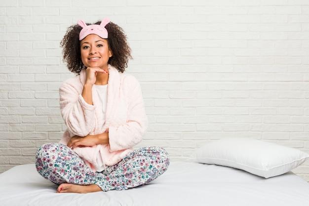 Młoda amerykanin afrykańskiego pochodzenia kobieta w łóżku jest ubranym pijama ono uśmiecha się szczęśliwego i ufnego, wzruszający podbródek ręką.
