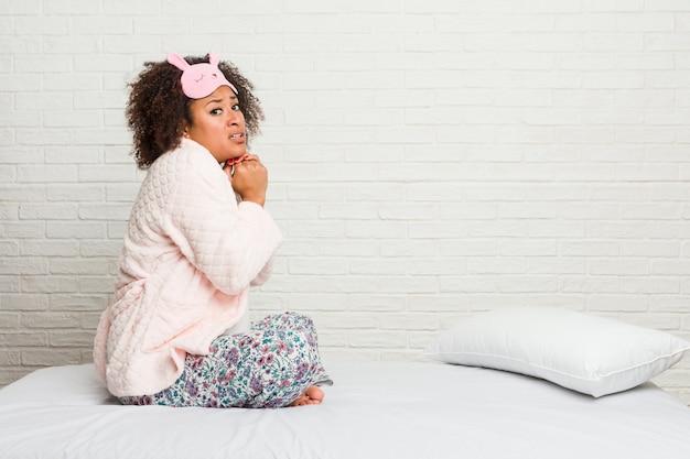 Młoda amerykanin afrykańskiego pochodzenia kobieta w łóżku jest ubranym pijama przestraszoną i przestraszoną.
