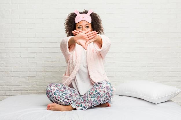 Młoda amerykanin afrykańskiego pochodzenia kobieta w łóżku jest ubranym pijama robi zaprzeczenie gestowi