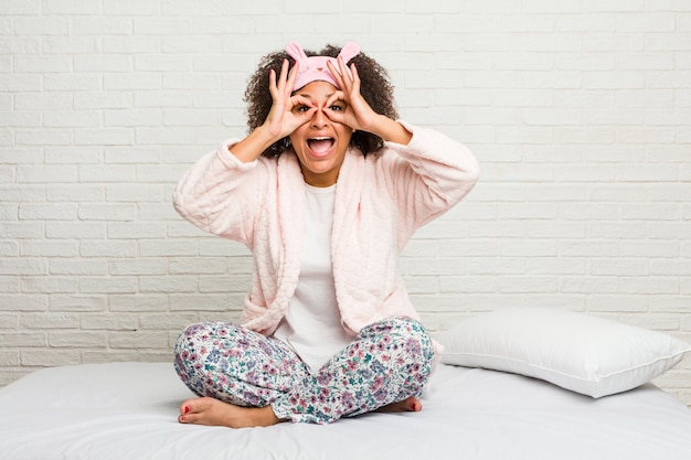 Młoda amerykanin afrykańskiego pochodzenia kobieta w łóżku jest ubranym pijama seansu ok podpisuje oczy