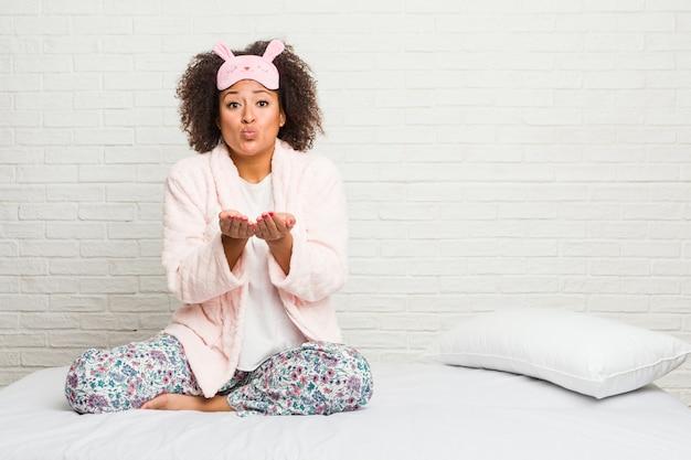 Młoda amerykanin afrykańskiego pochodzenia kobieta w łóżku jest ubranym pijama składane wargi i trzyma dłonie wysyłać lotniczego buziaka.
