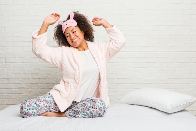Młoda amerykanin afrykańskiego pochodzenia kobieta w łóżku jest ubranym pijama świętuje specjalny dzień, skacze i energicznie podnosi ręki.