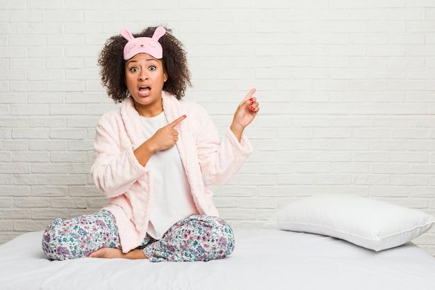 Młoda amerykanin afrykańskiego pochodzenia kobieta w łóżku jest ubranym pijama szokuje wskazywać z palcami wskazującymi