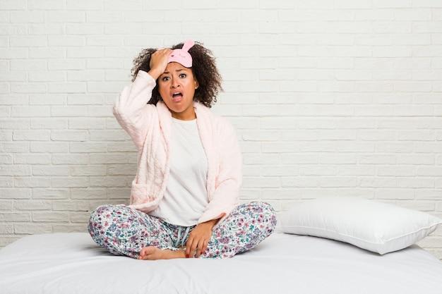 Młoda amerykanin afrykańskiego pochodzenia kobieta w łóżku jest ubranym pijama szokuje