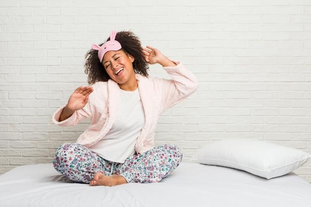 Młoda amerykanin afrykańskiego pochodzenia kobieta w łóżku jest ubranym pijama tana i ma zabawę.