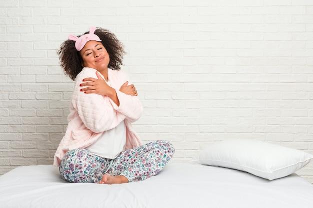 Młoda amerykanin afrykańskiego pochodzenia kobieta w łóżku jest ubranym pijama uściśnięcia, ono uśmiecha się beztroski i szczęśliwy.