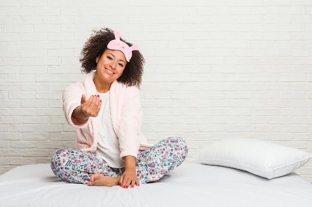Młoda amerykanin afrykańskiego pochodzenia kobieta w łóżku jest ubranym pijama wskazuje palcem na ciebie, jakby zapraszający zbliża się.