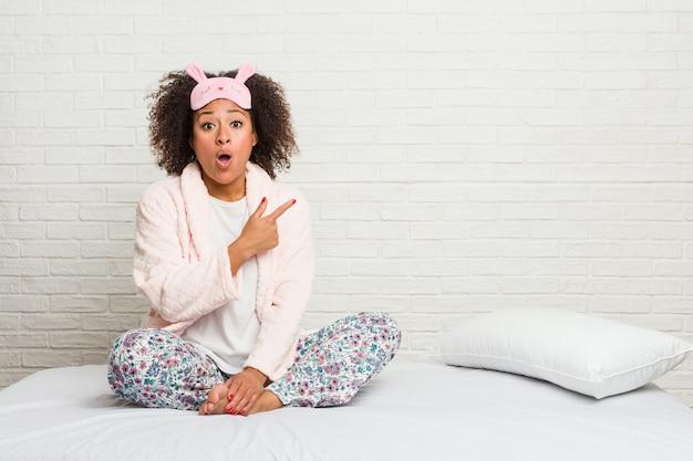 Młoda amerykanin afrykańskiego pochodzenia kobieta w łóżku jest ubranym pijama wskazuje strona