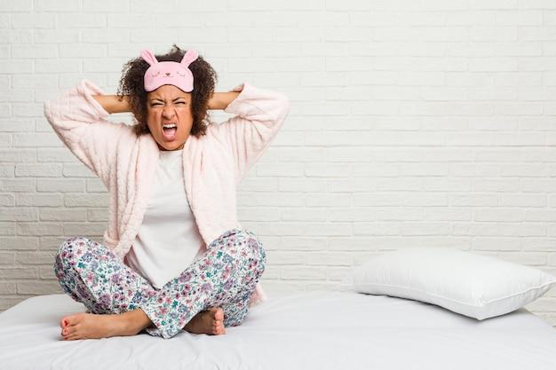 Młoda amerykanin afrykańskiego pochodzenia kobieta w łóżku jest ubranym pijama zakrywającą ucho z rękami próbuje nie słyszeć zbyt głośnego dźwięku.