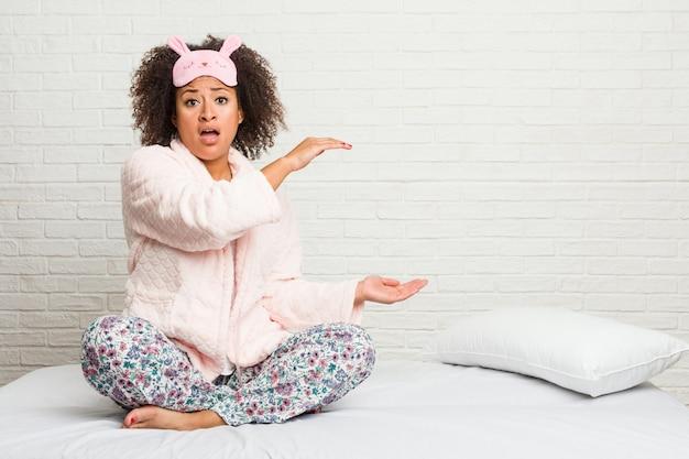 Młoda amerykanin afrykańskiego pochodzenia kobieta w łóżku jest ubranym pijama zszokowanego i zdziwionego trzymającego między rękami.