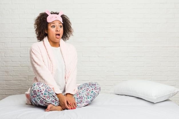Młoda amerykanin afrykańskiego pochodzenia kobieta w łóżku jest ubranym pijama zszokowany z powodu czegoś, co widziała.