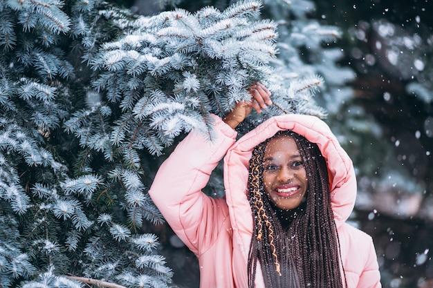 Młoda amerykanin afrykańskiego pochodzenia kobieta w zimie outside w parku