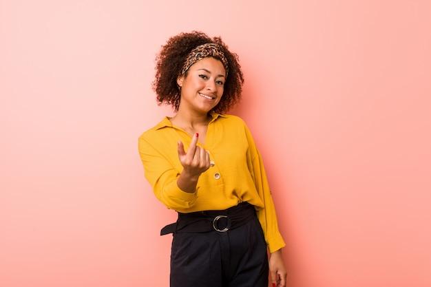 Młoda amerykanin afrykańskiego pochodzenia kobieta wskazuje z palcem na ciebie jakby zapraszający zbliża się.