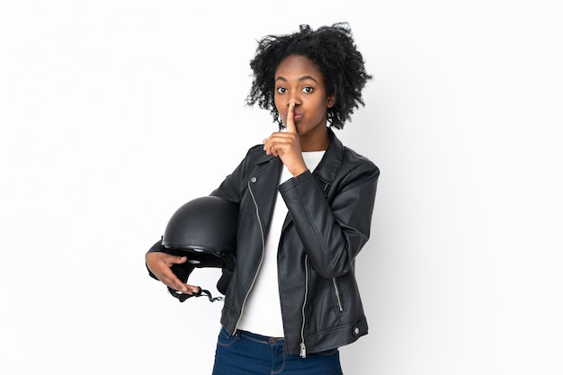 Młoda amerykanin afrykańskiego pochodzenia kobieta z hełma motocyklem odizolowywającym na biel ścianie robi cisza gestowi