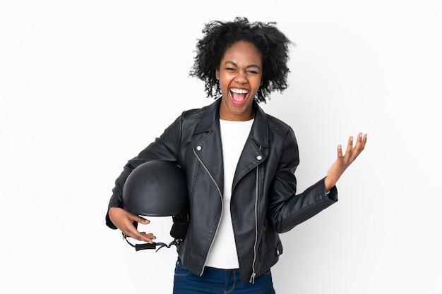 Młoda amerykanin afrykańskiego pochodzenia kobieta z hełmem motocyklowym odizolowywającym na biel ścianie nieszczęśliwej i sfrustrowanej z czymś