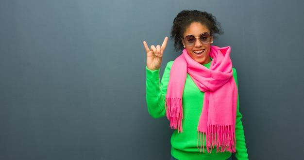 Młoda amerykanin afrykańskiego pochodzenia kobieta z niebieskimi oczami robi rockowemu gestowi