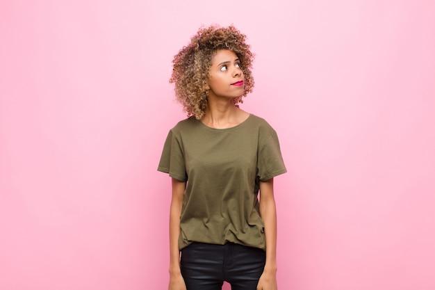 Młoda amerykanin afrykańskiego pochodzenia kobieta z zmartwionym, zmieszanym, nieświadomy wyrazem, patrzejący do kopii przestrzeni, wątpiący przeciw różowej ścianie