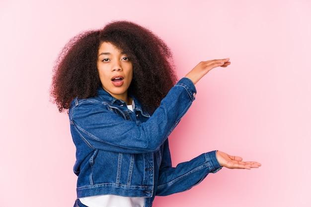 Młoda amerykanin afrykańskiego pochodzenia kobieta zszokowana i zdziwiona trzymająca pustą przestrzeń między rękami.