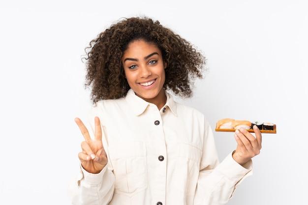 Młoda amerykanin afrykańskiego pochodzenia kobiety mienia suszi odizolowywający na bielu uśmiecha się zwycięstwo znaka i pokazuje