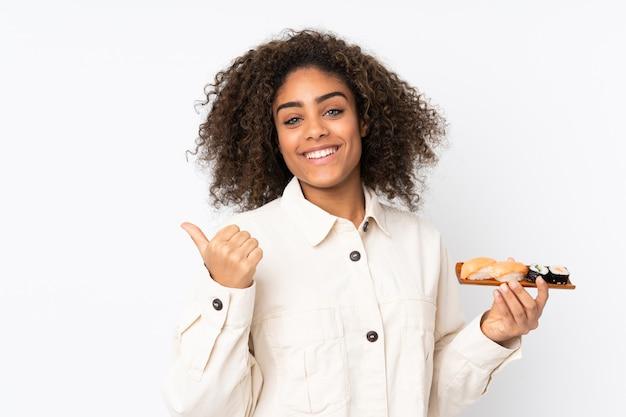 Młoda amerykanin afrykańskiego pochodzenia kobiety mienia suszi odizolowywający na bielu wskazuje z boku przedstawiać produkt