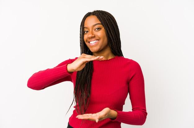 Młoda amerykanin afrykańskiego pochodzenia kobiety mienie coś z oba rękami