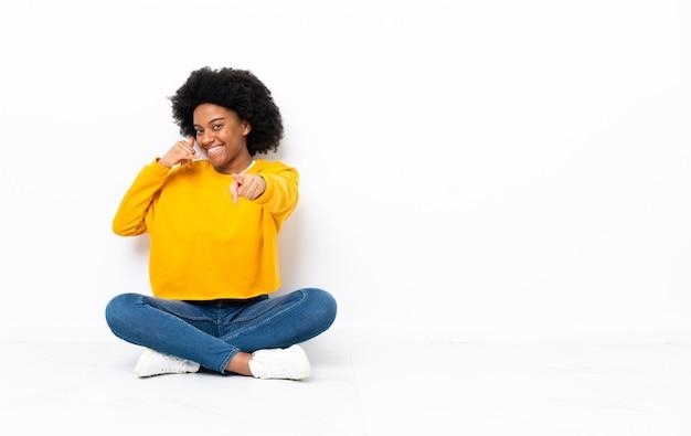 Młoda amerykanin afrykańskiego pochodzenia kobiety obsiadanie na podłoga robi telefonu gestowi i wskazuje przód